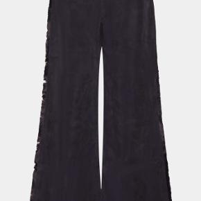 Højtaljede, straight fit bukser i sort/ meget mørk navy blå. Vidde ben, frynser i siden. Materialet er sandvasket cupro. Usynlig lynlås i siden.  Bukserne er mærket 'S', men er nærmere en 'XS'.  Brugt og vasket en gang.