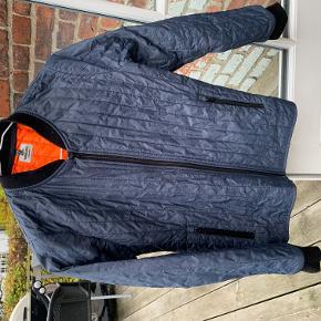 Den klassiske, quiltede Mads Nørgaard-jakke i mørkeblå med orange foer. Str. 12 år. Brugt, men i fin stand uden pletter, huller mv. og vasket i Svanemærket, ingen tumbling, ingen røg.