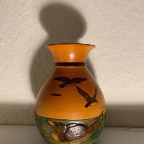 Hej! Jeg sælger denne fine Ibsen vase. Den er med fuglemotiv samt andemotiv. Det er 1. sortering, og har nummer 476. Denne vase er næsten fejlfri, og har kun et lille hak under sig, men det ses ikke når den står fint som en vase! Den er 18 cm høj, og har en diameter i toppen på 8,5 cm. Jeg sælger den til 250 kr. Hvis du har nogle spørgsmål til vasen så spørg løs.  Tjek gerne mine andre annoncer ud for en masse billige ting!
