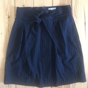Fin mørkeblå nålestribet nederdel. Lukkes bagpå med lynlås og lille knap. Bindebånd og lommer foran.