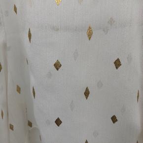 Yndig skjorte i sart stof. Den er ikke brugt vildt meget. Men der skal ikke meget til før en lille snor løber. Man kan se ved billedet af ærmet at der er løbet lidt tråde. Det er der generelt ved ærmerne og kanten i bunden. Ellers er den fin. Jeg kan ikke se nogle tråde der er løbet på selve skjorten og bindebåndet og de fine guld detaljer er så meget værd stadigvæk ved denne feminine skjorte.