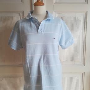 Polo t-shirt, Tommy Hilfiger slim fit, str. 40, God men brugt  Polo shirt i lyseblå med hvide striber. Unisex. Vintage. Selvfølgelig ren og pletfri. Størrelse L. Længde foran: cirka 66 cm. Materiale: 100% bomuld Eventuel fragt lægges oveni: 38 med DAO til nærmeste posthus/butik.