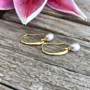Smukke klassiske øreringe i nikkelfrit materiale.  Perlen er en flot ferskvandsperler i str 6x7 mm (kan variere en lille smule)  Forgyldte