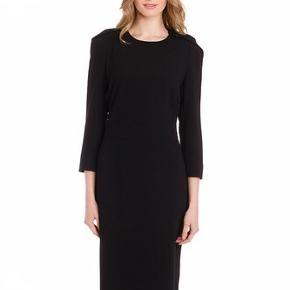 Smuk og elegant kjole fra Malene Birger. Modellen hedder Zefiro Kjolen er fremstillet i en polyester kvalitet med viskose foer. Kjolen lukkes bagpå med en skjult lynlås og hægte.  Der er en lille slids forneden bagpå. Det betyder, at kjolen bliver lettere at gå i. Kjolen har smarte detaljer med skuldre. Jeg har medtaget et foto af kjolen i blå, da man bedre kan se de smukke detaljer på dette foto. Min kjole er sort. Mål: Brystvidde ca 2 x 44 cm Talje ca 2 x 34 cm Ryglængden ca 98 cm Indvendig ærmelængde ca 35 cm (3/4 ærmer). Det er en str. 32, men jeg synes det svarer til en normal str 34. Kjolen har kun været brugt til 2 lejligheder og fremstår i rigtig fin stand.