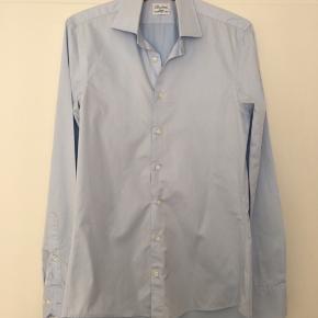 Lyseblå slimline skjorte fra Stenstrøms str. 15/38. Skjorten er kun brugt enkelte gange. Der er et lille hul bag på højre ærme, men det ses ikke inden under en trøje eller jakke.   Nypris 1300kr. Afhentes i Gentofte eller sendes på købers regning.
