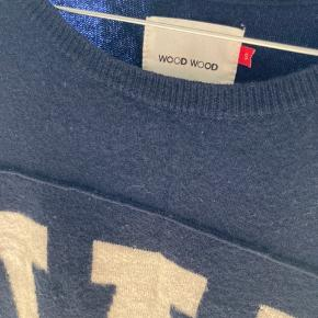 Lækker sweater i 100% uld fra Wood Wood m. logo foran og striber på armene.   Brugt nogle gange, men fremstår stadig rigtig flot og uden slid