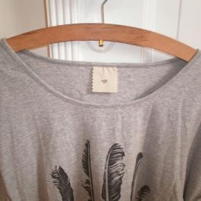 Varetype: Grå T-shirt top print fjer bomuld bluse Størrelse: 40 L Farve: Gråmeleret sort  Skøn T-shirt fra Heartmade i 95% bomuld og 5% elastan. Størrelsen er klippet ud, men den passer en dansk str. 40 L. Kan dog også bruges af en mindre størrelse, så sidder den lidt mere oversize. Tjek dog mål for en sikkerheds skyld. Brystmål: 53 cm på tværs fra armhule til armhule (dvs 106 cm i omkreds). Længde: 62 cm målt fra nakken og ned. Brugt, men fremstår i pæn stand uden huller, pletter, markant fnuller eller lignende.