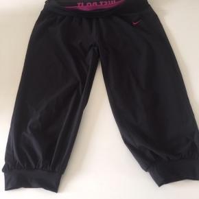Sort 3/4 lang Nike Dri-Fit træningsbuks. Løs model m/pink Nike logo, rib forneden og bred rib i taljen.   Længde: ca. 72 cm.