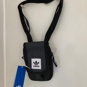 Sort mindre unisex crossbody fra Adidas Model Map Bag Lang regulerbar rem som kan spændes ud til minimum 130 cm Model har foruden det lidt større rum desuden xtra for og baglomme. Højde ca 17,5 cm Bredde knap 11 cm Sælges for 150 pp