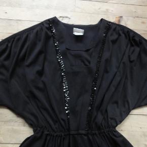 Vintage retro kjole med pailletter af mærket Sabrina. Den er meget vid om brystet fordi den har flagermusærmer og jeg tænker den også vil passe en 42 eller 44. I taljen måler den 60 - 130, om rumpen 200+ og den er 114 lang. Farve: sort