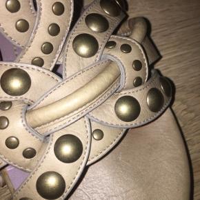Sonia Rykiel sandal  Nypris 4200,-  Den smukkeste sandal fra Sonia Rykiel i str. 39. Dette er en sjælden model. Veto cuoio.  Farven er taupe (creme / beige). Dens overdel og ydersål er i læder. Foret og indersålen er ligeledes i læder, så skoen er meget behagelig at have på. Skoen har forskellige nitter påsat. Skoen lukkes med et spænde.   Jeg har fået sandalen forsålet, da dens skøbelige lædersål ville blive skadet ved brug.   Jeg købte disse sandaler, da jeg forelskede mig i dem, men jeg har desværre ikke kunnet bruge dem, da de er for smalle til min fod.