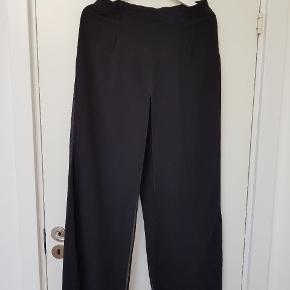 Sorte løse højtaljede bukser i crepe. Det yderste lag er løst. Str. L , men nærmere medium.
