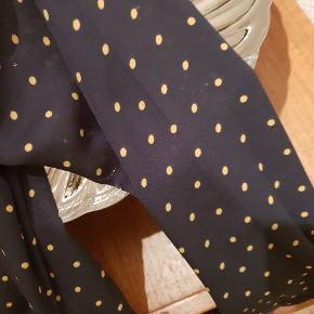Fin slå om-bluse i mørkeblå med gule prikker og flot halsudskæring.