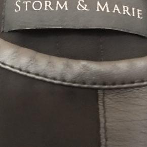 Skjorte-bluse str. 38. Brugt 2-4 gange. Farven er nok grå/sort med en sort læder stribe midt på.