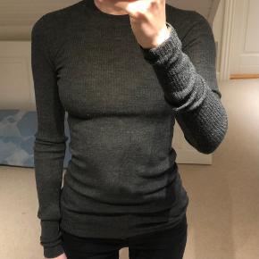 Ribstrikket tætsiddende bluse fra H&M studio i str 36. Blusen er i rigtig fin stand og lavet i 100% uld.  Er åben for bud!