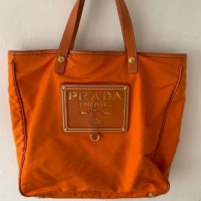 Læder & nylon taske. Orange læderkanter Orange nylon for   Meget god stand - er vedligeholdt med omhu. Den ydre bund på højre side har nogle tegn på slid. Skulderstroppen er aftagelig og kan bæres i hånden.  Er vintage