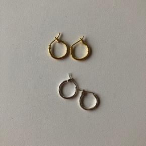 Fine små øreringe i messing eller sølvfarvet (ikke ægte sølv) Aldrig brugt. Hvis de skal sendes kan jeg gøre det for 9 kr på købers regning.   Pr par 25 kr  2 par 40 kr