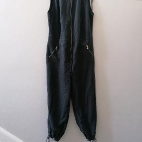 Sort buksedragt med lynlås og lommer. Der står str 22 i den men svarer til 46-48. Uden stræk