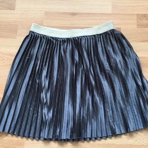 Superlækker plisseret nederdel i mørkegrå/guld.