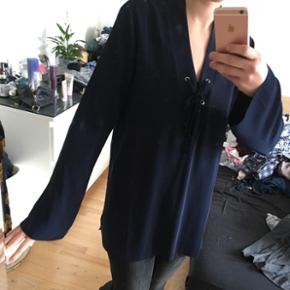Rigtig fin mørkeblå top fra envii. Har lidt trompet ærmer og derudover et loose fit og rigtig fin til jeans. Bånd ved brystet.