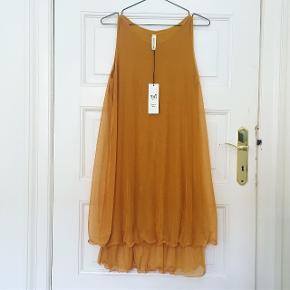 Lækker og blød karrygul kjole - aldrig brugt. Længde ca. 93cm. Bryst ca. 50cm. 50% polyester, 45% viskose, 5% elasthan.  Sender gerne.