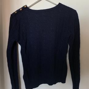 Klassisk navy-farvet sweater fra Ralph Lauren med seje guld-knapper på den ene skulder. Sweateren er brugt, men er i fin stand.