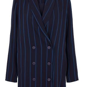 Cool navy blazer fra Just Female. Den har kobolt-blå striber, en oversize pasform, v-udskæring ved brystet, tydelig knappe-åbning på forsiden, samt lommer.   Kvalitet: 95% Polyester, 5% Viscose