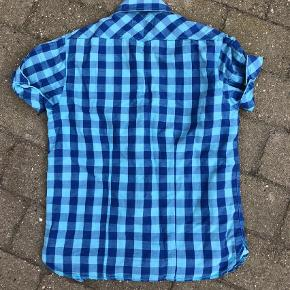 Scotch Soda blå kortærmet skjorte.  Super fed ternet skjorte med korte ærmer og mange fede detaljer. Desværre er den nederste knap gået i udu. Super pæn stand.  Pris : 60 kr pp