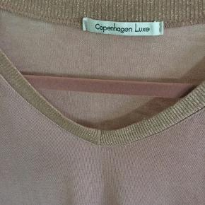 Fin strik i rosa v hals bluse med guld glimmer i kanterne fra CPH Luxe str L  men lille i str passer str S/M, brugt meget lidt fejler intet, nypris 399 kr.  Pris 80 + evt porto