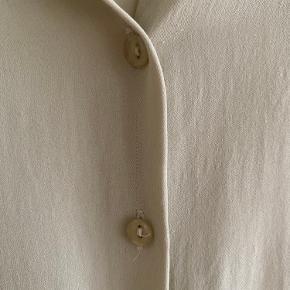 Vintage/ retro/ secondhand/ genbrug bluse/ top/ kortærmet skjorte i beige.    100% silke   I god, smuk vintage stand.   Kan passes af en xs-m  Længde: 50 cm Bryst: 48 cm x 2 Talje: ca. 46 cm x 2  Kan sendes eller afhentes i Mårslet eller Aarhus C efter aftale.  Se også mine andre annoncer fra bl.a. Weekday, Gina Tricot, H&M, Ganni, Tiger of Sweden, Rosemunde, With Jean, Rude, Faithful the Brand, COS, Zara, FWSS og vintage/ retro