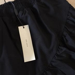 Neo Noir sort nederdel Model: Barnsley solid skirt  Farve: Sort Størrelse: M / medium Købspris: 399,-   Smuk sort nederdel fra Neo Noir i et super feminint design med små flæser forneden og et asymetrisk snit foran. Nederdelen har en smal elastikkant foroven, og det smukkeste fald.   Pasform: Almindelig i størrelse  Farve: Sort Kvalitet: 100% Polyester  Vask: 30°  Stylingtips: En dejlig let nederdel at style. For et festligt look miks med en smuk blondebluse og dress up med et par høje hæle. Skal du bruge nederdelen til hverdag, miks den med en lækker strikbluse eller en casual skjorte.  For et sporty udtryk tilsæt en sneakers, dette skaber kontrast til det feminine look. Lækker sort nederdel, der kan styles til det meste. Miks med både sweatshirt, t-shirt, toppe m.m. En meget alsidig nederdel, der er super nem at style.   #30dayssellout