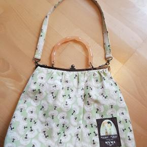 Fin stoftaske fra Noa Noa, vintage look. Plastik bøjle til håndtaske og stof rem til skuldertaske. Kun brugt få gange... pæn stand også indvendig, se fotos. Bred 38 cm Høj 30 cm (med hank 40 cm) (med rem 65 cm)