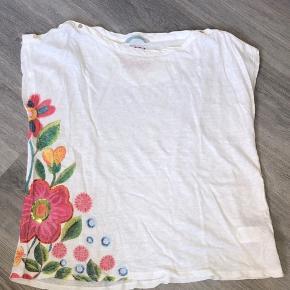 Sød, lettere transparent top. Søde blomster og knapper på skuldrene. Aldrig brugt. Omkreds bryst 110 cm Fuld længde 59 cm