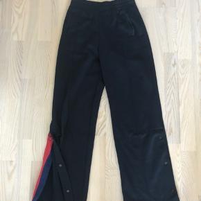 Elegante, højtaljede mørkeblå bukser. Kan knappes op forneden med fin rød detalje i syningen på indersiden. Fitter en str XS-M, da de er lange.
