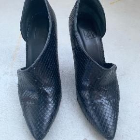 Genuine leather, snake like, heals 9 cm. Used a couple of of times & are in a very good condition.