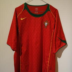 Portugal trøje fra da de var værtsland til EM 2004. De havde dengang både Figo og en ung Ronaldo i truppen, som førte dem til finalen hvor de tabte til Grækenland.   Tags: fodbold, fodboldtrøje, fodboldtrøjer...