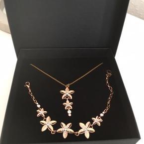 """Fint smykkesæt mrk. Pilgrim. Halskæde og armbånd. Aldrig brugt ! Rosaguld/rosegold/rosa guld med fine små diskrete """"diamanter"""", som gør smykkerne helt unikke.  Købspris ca. 499,-"""