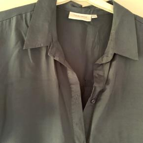 Skjortekjole i mørkeblå (let shiny) med korte ærmer og knapper ned foran.