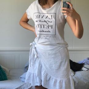 Hvid og sort t-shirt , bluse , top med skrift på fransk. Kan bruges som sommertøj      Kan passes af Xs - s - m