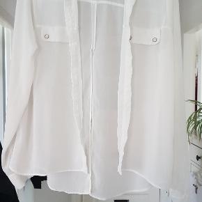 Råhvid polyester skjorte med stor slids i ryggen, let og luftig over kjolen til sommer. Perfekt til at binde. Længde: 59cm foran - 73cm bagpå. BM 2x50cm  Ærmer: 63cm
