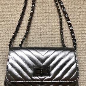 Lækker clutch i grå metallic med kæderem som kan fungerer i 2 længder.  Lækkert italiensk læder.  Ny pris 650,- Længde 18cm højde 9cm