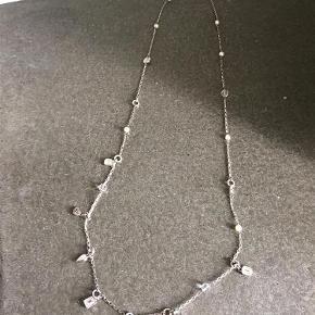 """Varetype: halskæde Størrelse: lang Farve: """"sølv"""" med sten Oprindelig købspris: 999 kr. Prisen angivet er inklusiv forsendelse.  Denne fine halskæde sælges, Har være brugt ca. 10 gange men jeg synes stadig den er fin. Den kan laves om til 2 korte kæder i stedet for. Der er små låse i begge sider af kæden.   Den er rigtig flot til en kjole eller top med v-hals.  bud og få en fin kæde til de kommende julefrokoster."""