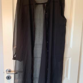 Lang skjorte i chiffon lignende materiale - gennemsigtig. 100% polyester.