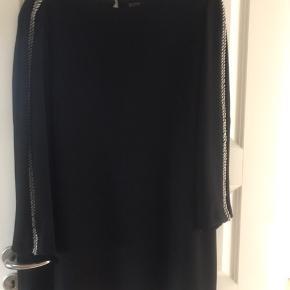 Lækker klassisk sort kjole. Bemærk der mangler en påsætning af pynt på venstre ærme øverst ved skulder