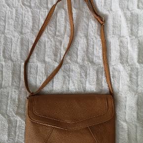 Fin lille brun fake læder taske. Stroppen kan indstilles. Der er en lille lomme indeni og tasken er stor nok, til alle str mobiler ☺️