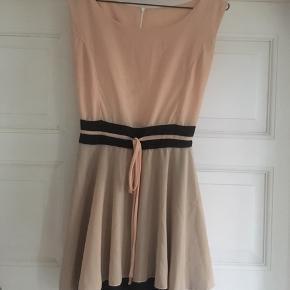Sød kjole i fersken og sort med bindebånd. Kan ikke finde et mærke, så jeg kan se fabrikant. Kan hentes i Århus C