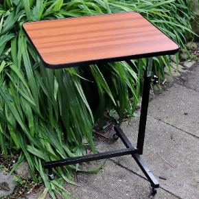 Lækkert sengebord, barbord eller serveringsbord. Lille retro bord i sort metalstel med teaktræslaminat. Bordpladen måler 50*40 cm og kan justeres mellem 55 og 70 cm i højden.
