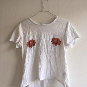 Dejlig, let T-shirt med farverige blomster på brysterne. Super fin og god til et casual look. Den er brugt få gange, og i god stand. Det er den klassiske hvide T-shirt, dog med de søde ekstra detaljer 🌸🌼