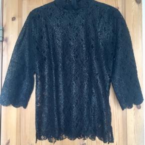 """Smuk og festlig blondebluse fra Gestuz i sort med """"guldstøv"""" (ses bedst på billede 3) Blusen går lidt op i halsen og har 3/4 ærmer. Lukkes med skjult lynlås i nakken. Blusen er kun brugt en gang og helt som ny.  Jeg foretrækker at handle via Trendsales og sende med DAO. Alternativt via MobilePay.  Køber betaler gebyr og fragt.  #30dayssellout"""