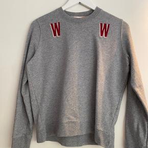 Grå sweater / bluse fra Wood Wood i str xs. Den er blevet brugt meget, og er blevet stiv i stoffet efter vask. Ellers er den fin. Den har en lille plet over det ene w